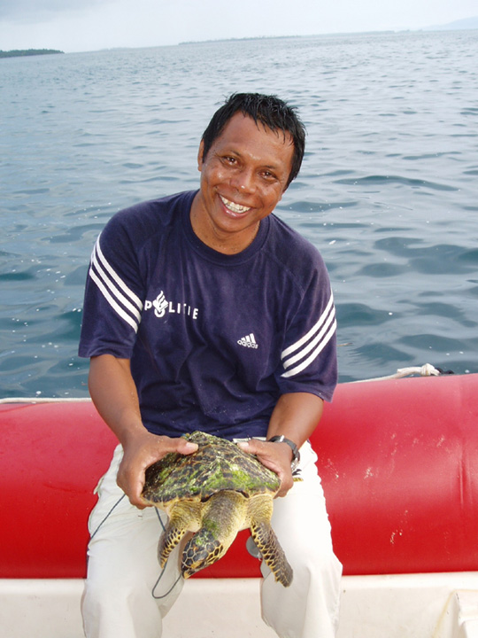 Asril Djunaidi who bought a hawksbill turtle from villagers and about to release it far from the village.