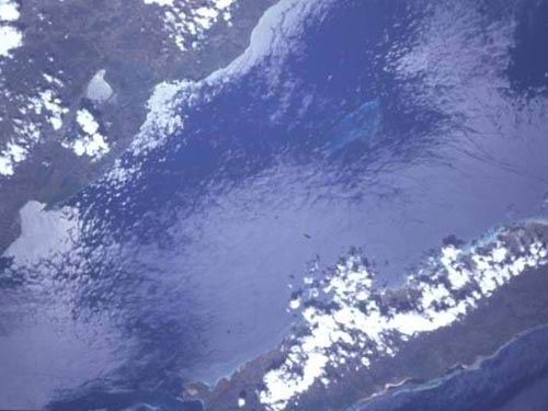 Canal du Sud and Ile de la Gonave.  Rochelois Bank can be seen in the center of the photo.  Sunglint accents wave patterns.  North is at approximately 5:00.
