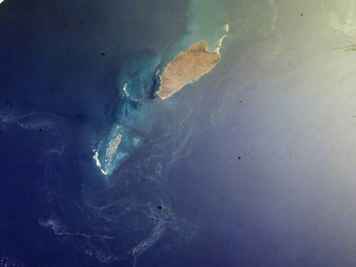 Barrow Island and the Monte Bello Islands, Western Australia.  North is at approximately 7:00.  Singlint lightens the upper right portion of the photo.  An algal bloom is also visible.