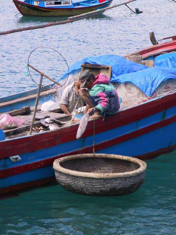 Unloading fish into a basket boat