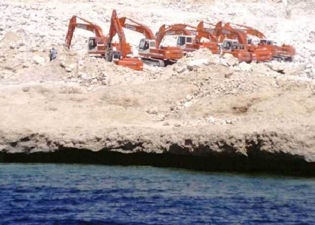 Heavy equipment moving sediment on a coastal construction site